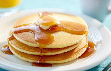 Short stack of breakfast pancakes with syrup and butter